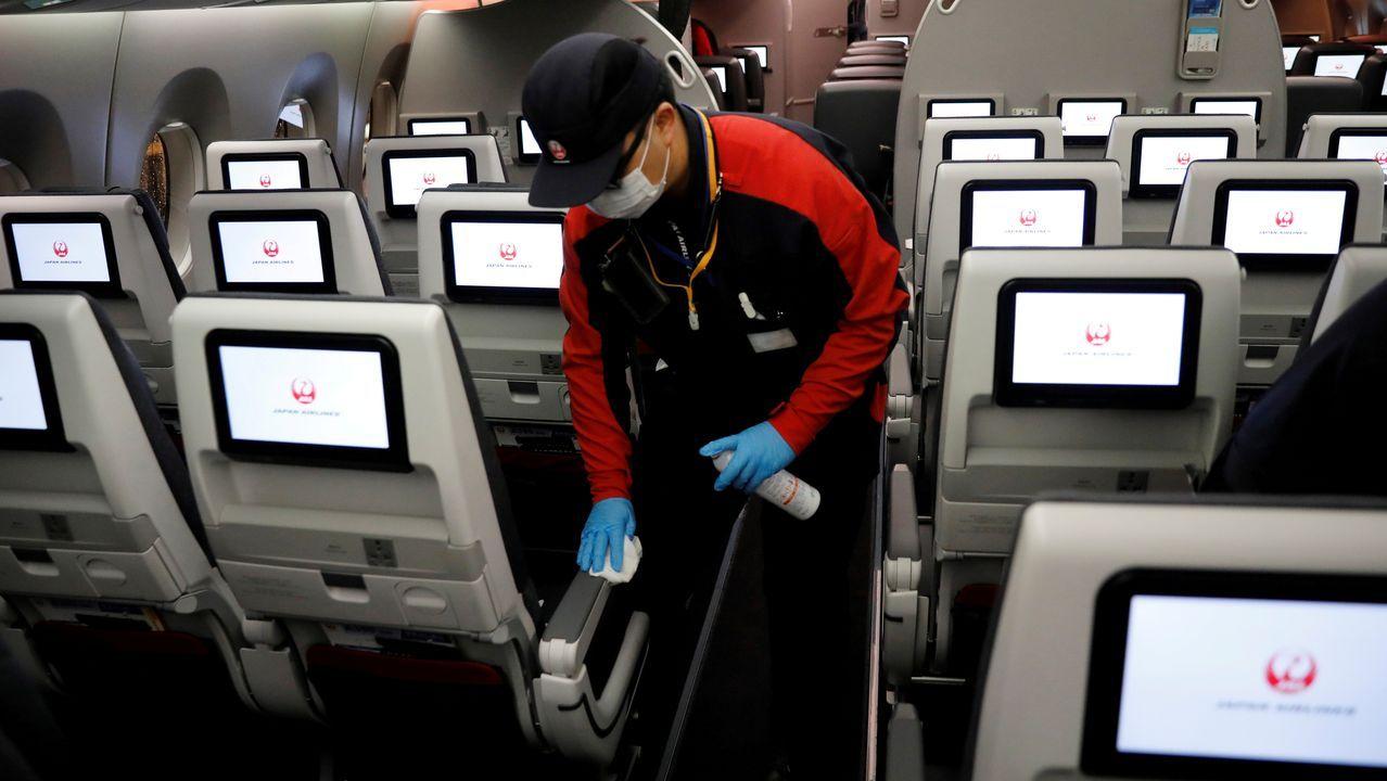Un trabajador de Japan Airlines desinfecta la cabina del avión tras un vuelo doméstico