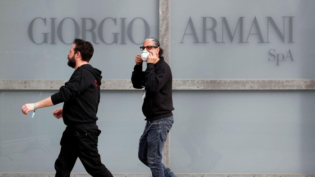 Un hombre colocándose una mascarilla en Milán, ante el rótulo de la marca textil