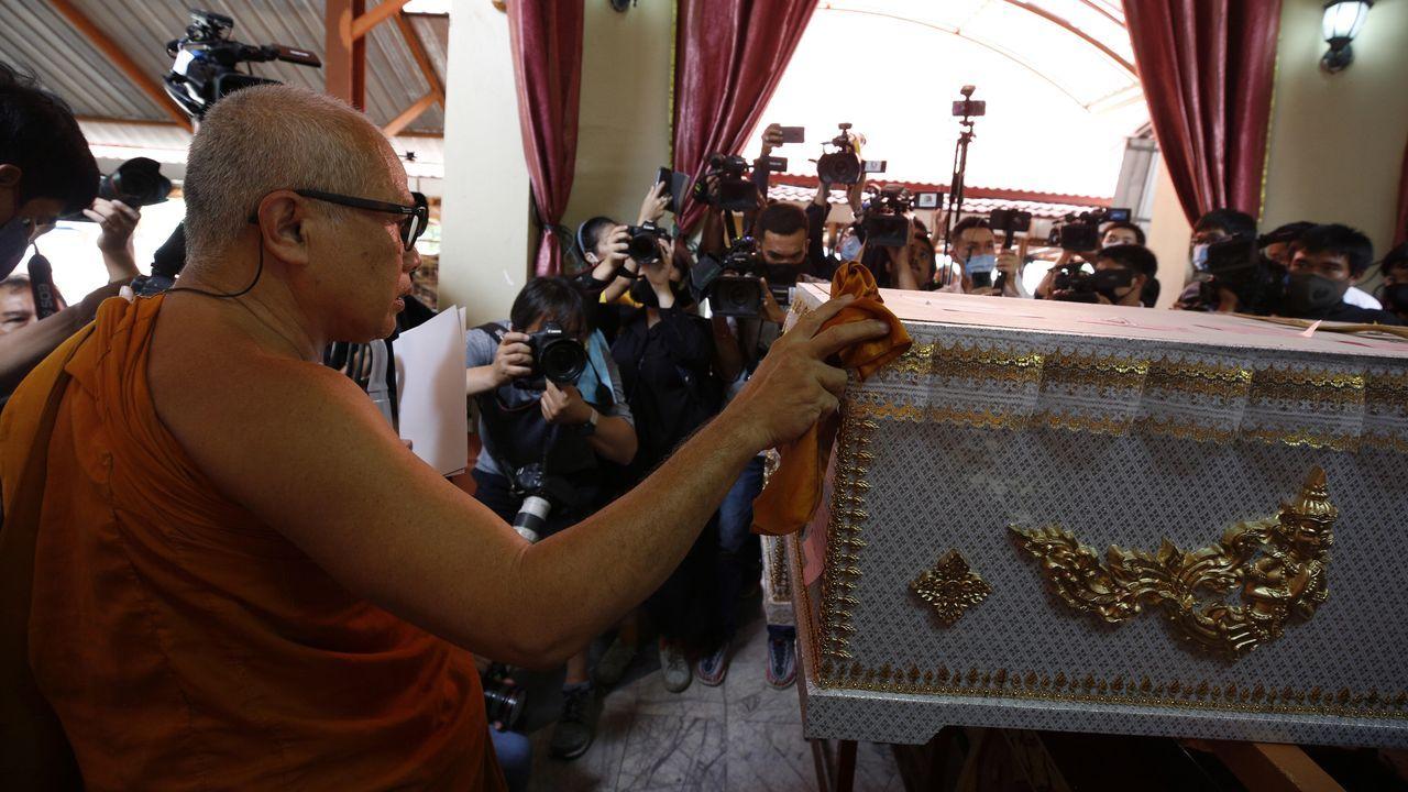 Un grupo de pasajeros consulta los vuelos en el Aeropuerto de Asturias.Un monje acompaña el féretro del caníbal de Nonthaburi