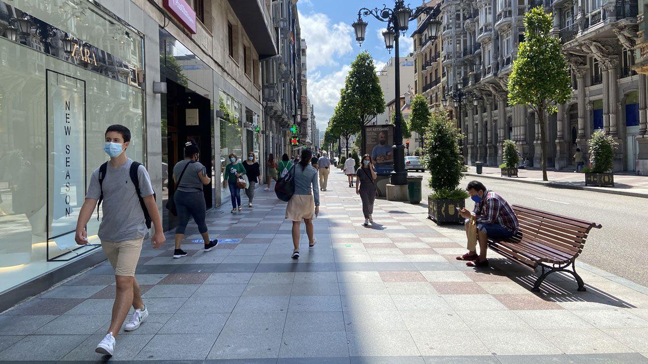 Varios transeúntes por la calle Uría de Oviedo, con la mascarilla puesta
