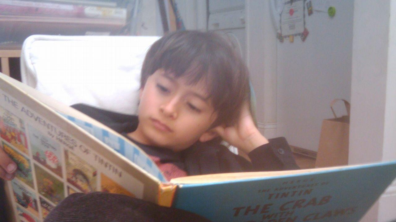 Un neno lendo un libro de Tintín