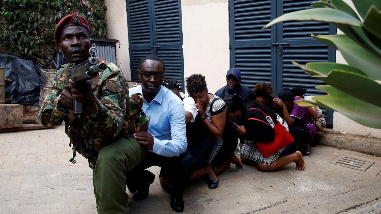 Un soldado protege a varios civiles en el en torno del hotel atacado