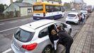 Los pequeños de Baamonde suben al coche mientras el autobús escolar pasa de largo.