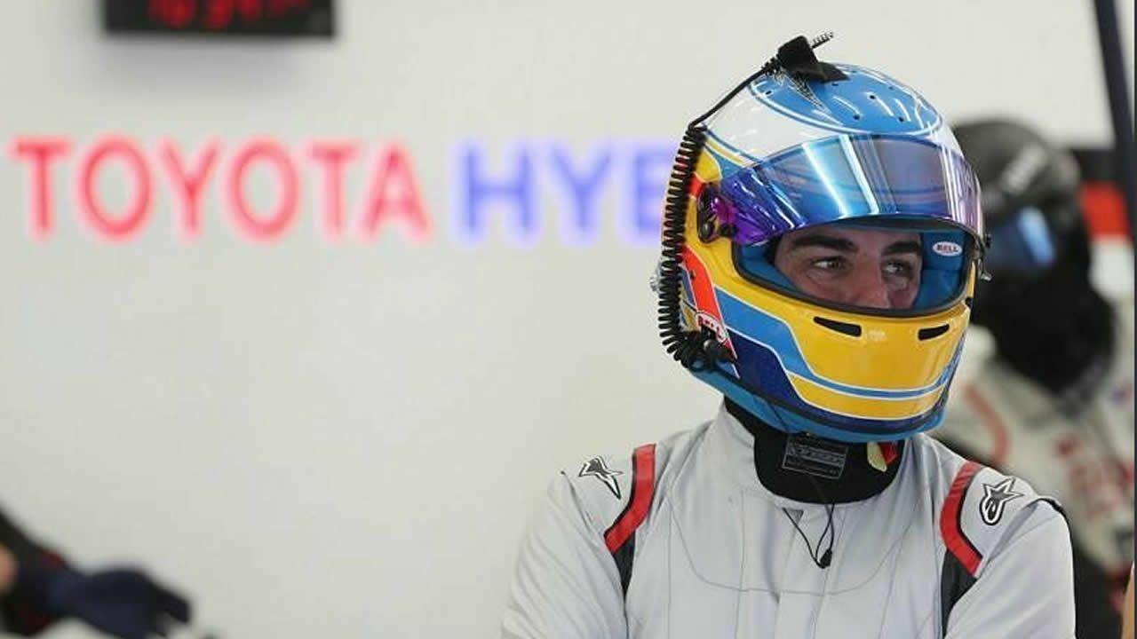 El piloto español Fernando Alonso del equipo United Autosports firma un autógrafo en Daytona Beach, en un cartel con su nombre