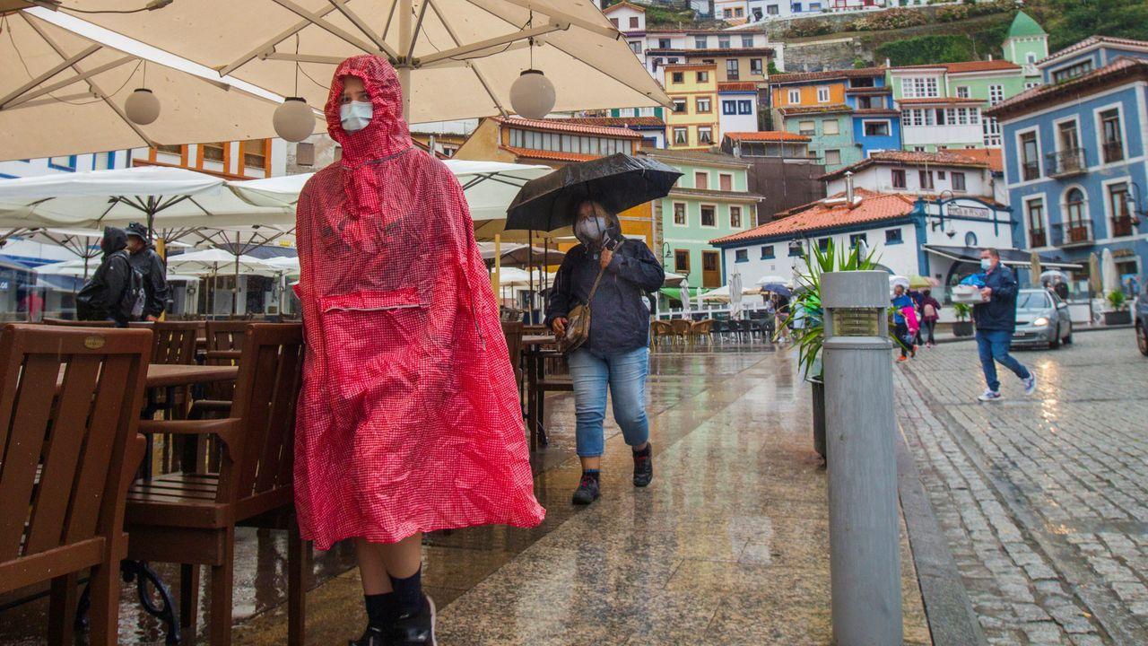 Carril de tren de Arcelor, en Veriña.Un grupo de turistas visita Cudillero bajo la lluvia