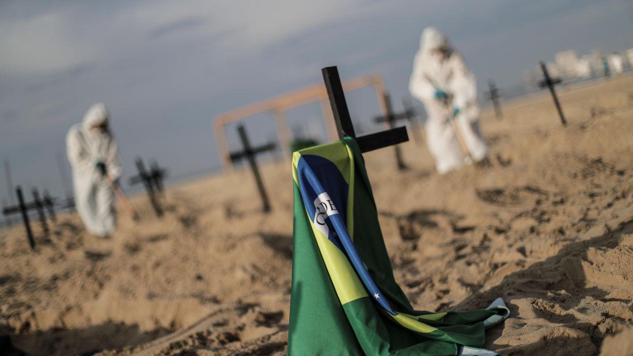 ctivistas colocan ciento diez cruces, como forma de denunciar los errores cometidos por el Gobierno en la gestión de la crisis del coronavirus, durante un acto organizado por la ONG Rio de Paz este jueves, en la playa de Copacabana, Río de Janeiro