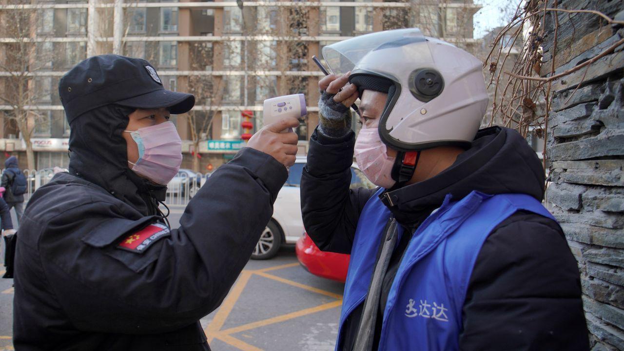 Un empleado de seguridad toma la temperatura a un ciudadano chino en Pekín. La capital ha establecido controles de salud en el metro y el tren