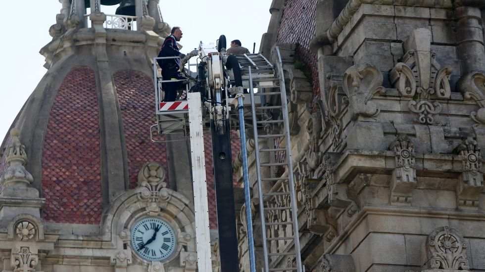 Los bomberos de A Coruña retiran con una grúa la vegetación de los tejados del Palacio de Maria Pita