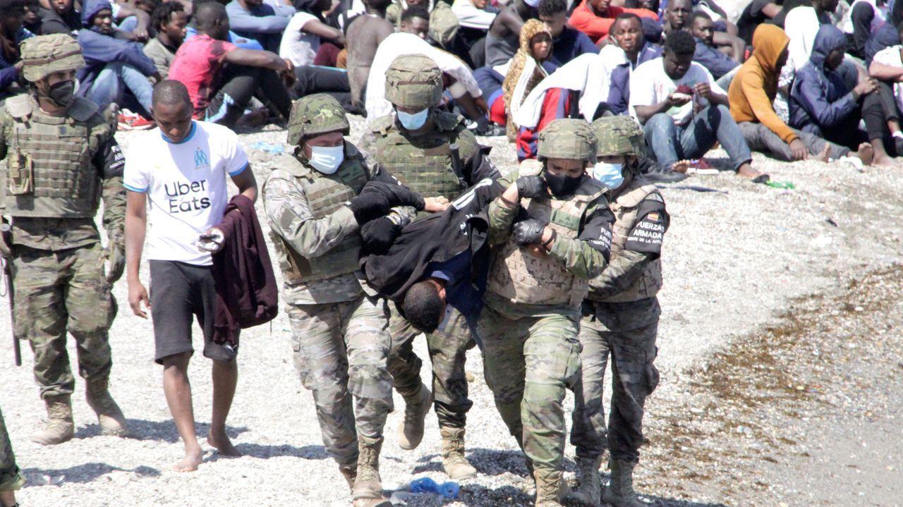 Un militar del ejército español ayuda a un menor migrante procedente de Marruecos a su llegada a Ceuta