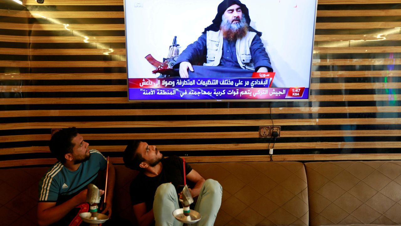 Dos iraquíes atiende a la noticia de la muerte del lider del EI, Abu Bakr al Bagdadi