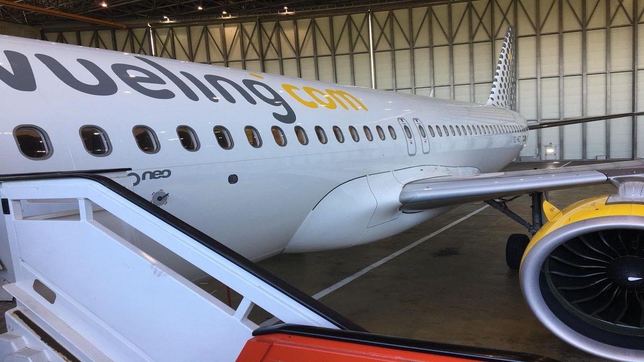 Un grupo de pasajeros consulta los vuelos en el Aeropuerto de Asturias.Un avión de la compañía Vueling