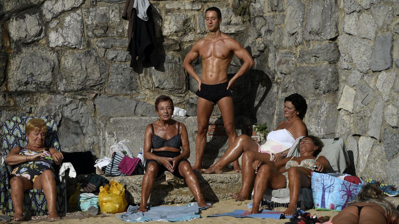 Gente tomando el sol en la playa de San Lorenzo, en Gijón
