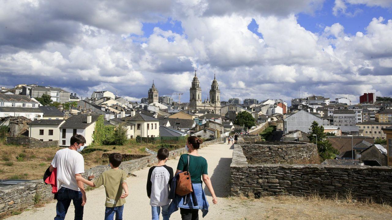 La hierba crece libre por el adarve de la Muralla.Turistas paseando el pasado verano por el adarve de la Muralla de Lugo