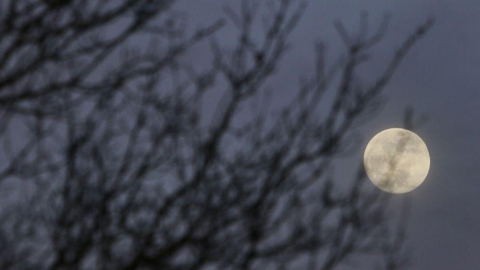 Pero ¿qué es una superluna azul?.Una superluna se ve através de un letrero luminso con el nombre de Asturias, en Siero