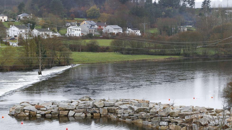 En el costado izquierdo de la pasarela se observa como el agua baja entre las rocas.