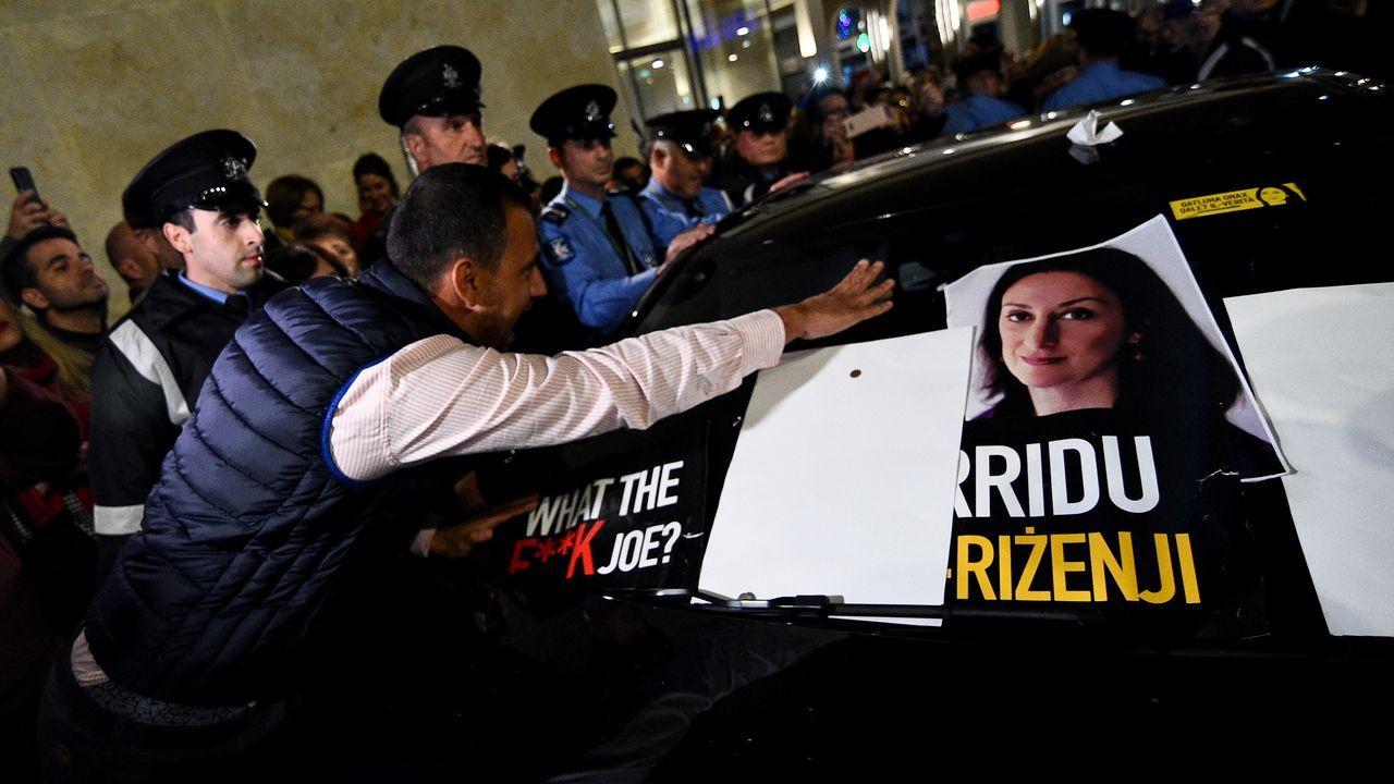Un manifestante pega una foto de la periodista asesianda en el automóvil del ministro de Justicia,, durante una manifestación para pedir la renuncia del  Muscat