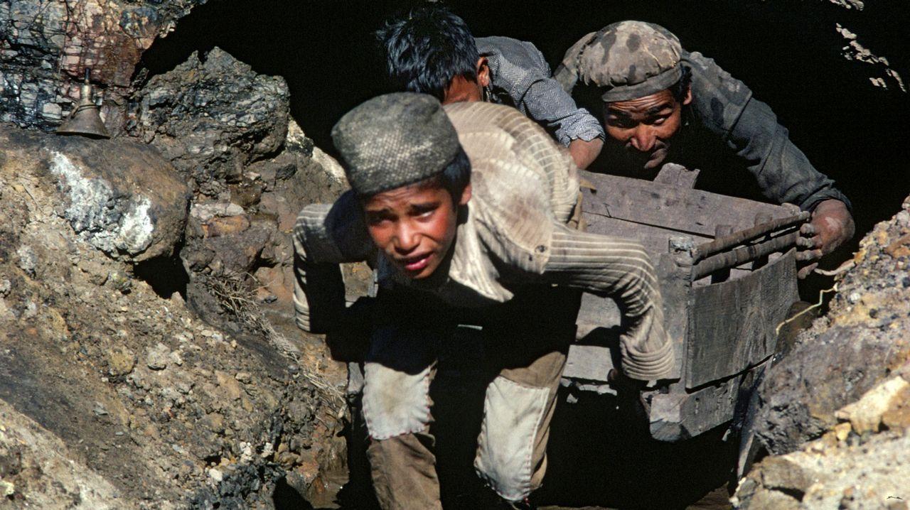 Nenos traballando con adultos nunha mina en Assam (a India)