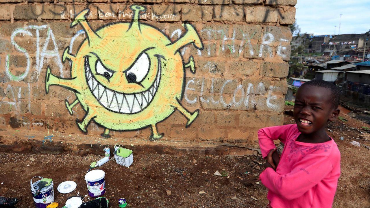 Un niño, en Nairobi ante un grafiti que alerta del coronavirus