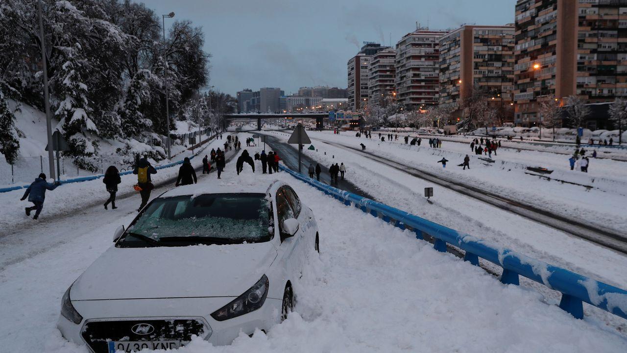 Un coche atrapados y peatones caminando por la M-30
