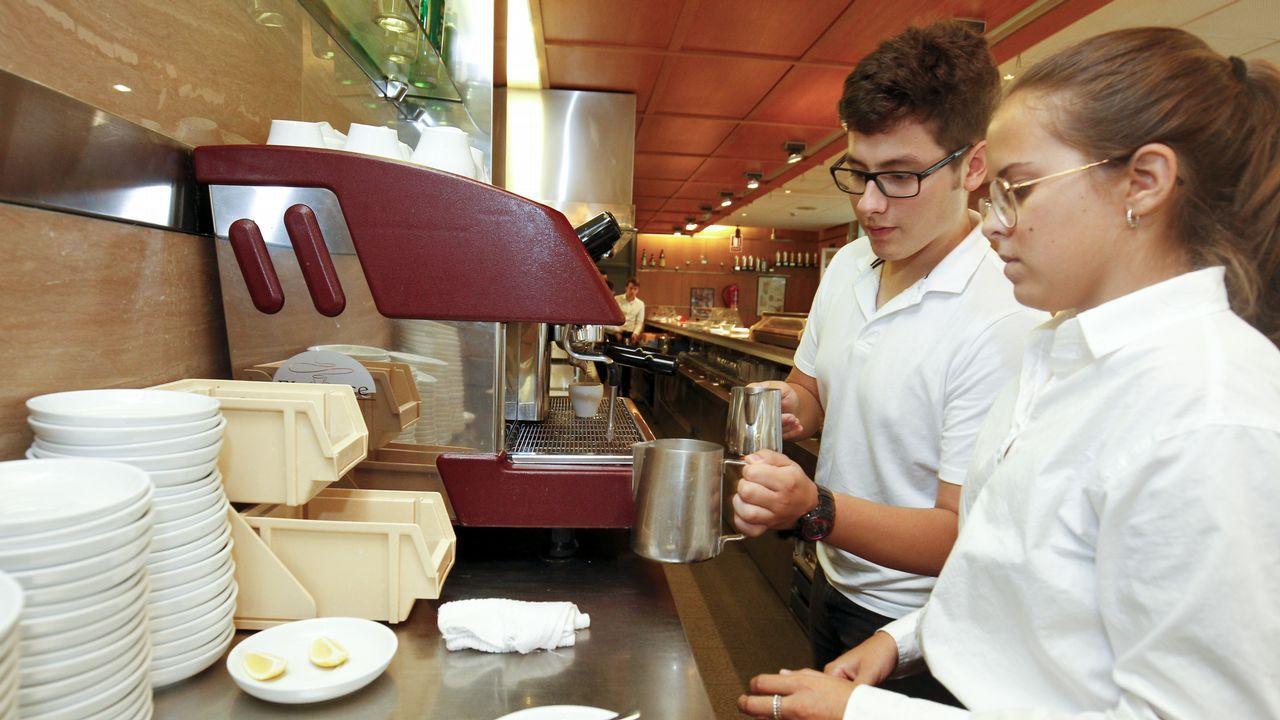 Dos jovencísimos alumnos aprenden a preparar café tras la barra de la cafetería del propio CSHG