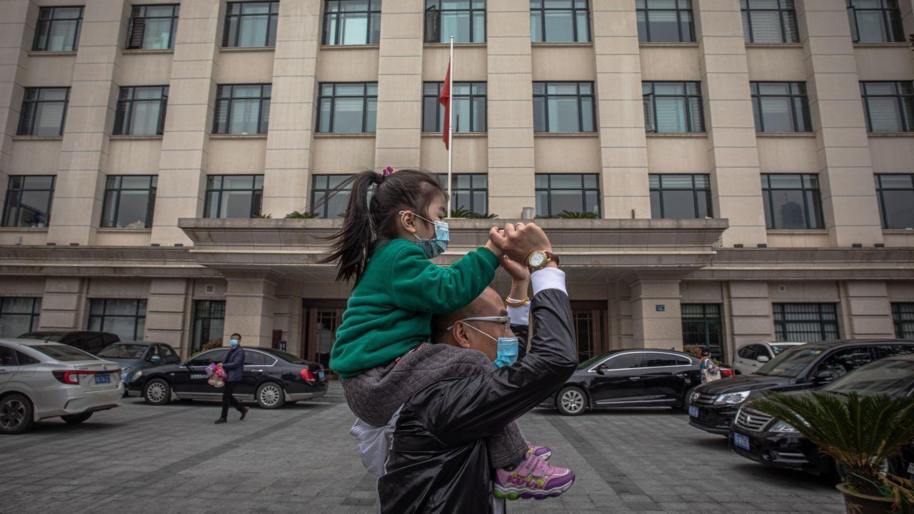 Un hombre lleva en hombros a una niña en la ciudad china de Wuhan