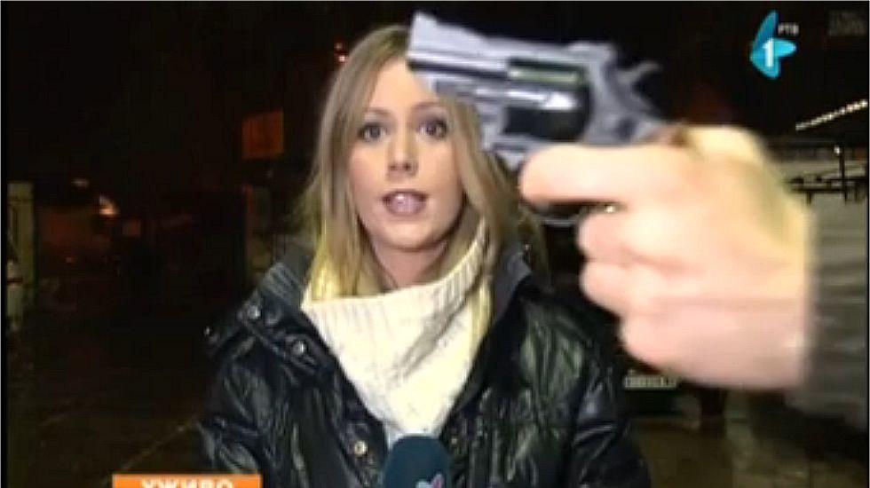 Un desconocido muestra una pistola a una reportera de televisión serbia en pleno directo