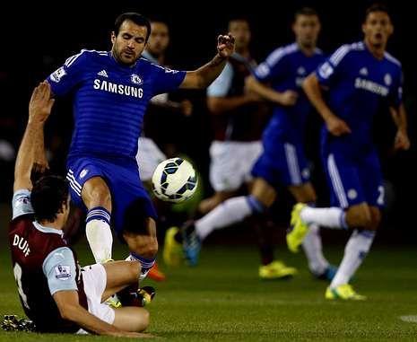 Mitroglou.Cesc intenta salvar la entrada de un rival durante el encuentro frente al Burnley.