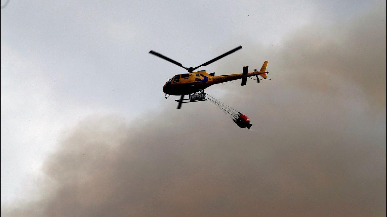 Un pirómano, cazado in fraganti en Asturias.Un helicóptero trata de sofocar un incendio en las proximidades de Naves (Llanes)