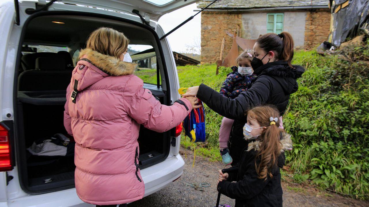 Uno de los taxis que realiza transporte escolar en Baralla recoge a dos niñas en un pequeño núcleo del municipio
