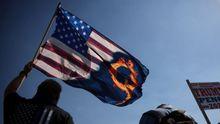 Un seguidor de Trump enarbola una bandera con el símbolo de la secta QAnon, promotora de una teoría de la conspiración en Estados Unidos