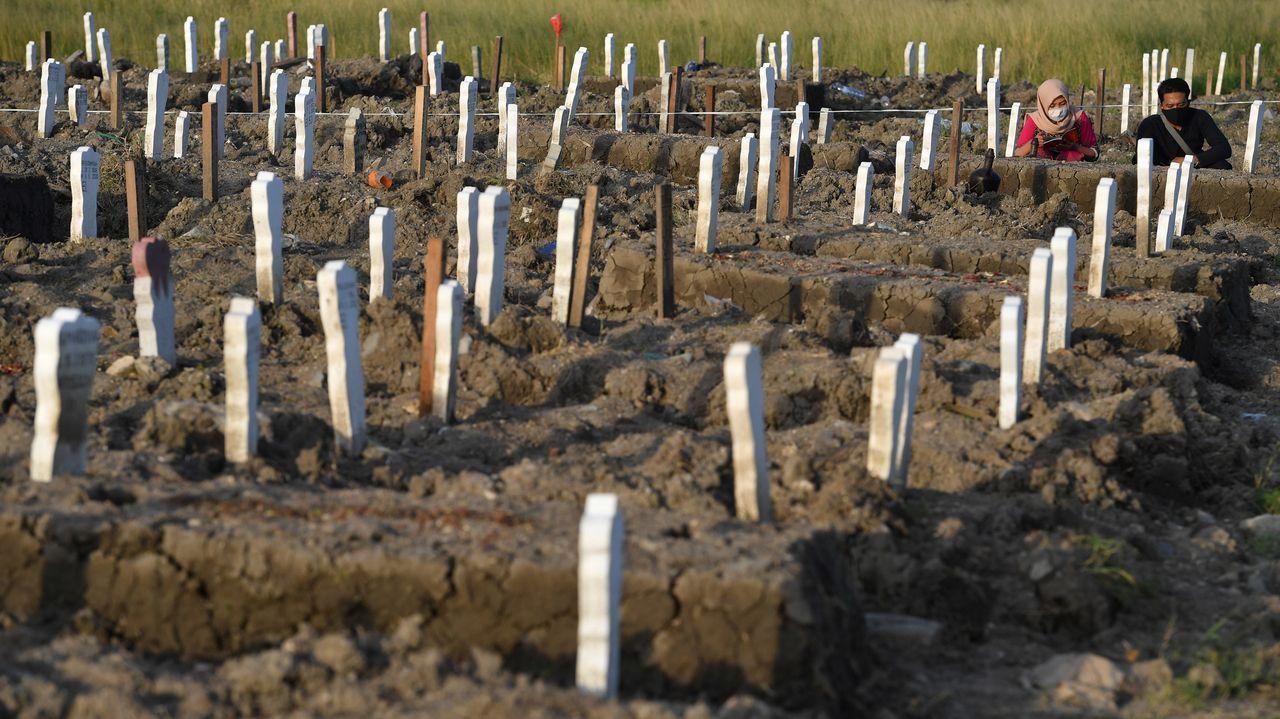 En Java, dos personas lloran ante la tumba de un familiar fallecido por covid-19