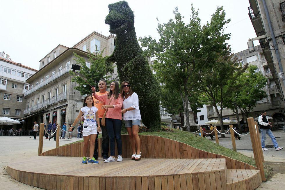 Una familia posa delante del Dinoseto, en la Porta do Sol, con un palo para realizar «selfies».