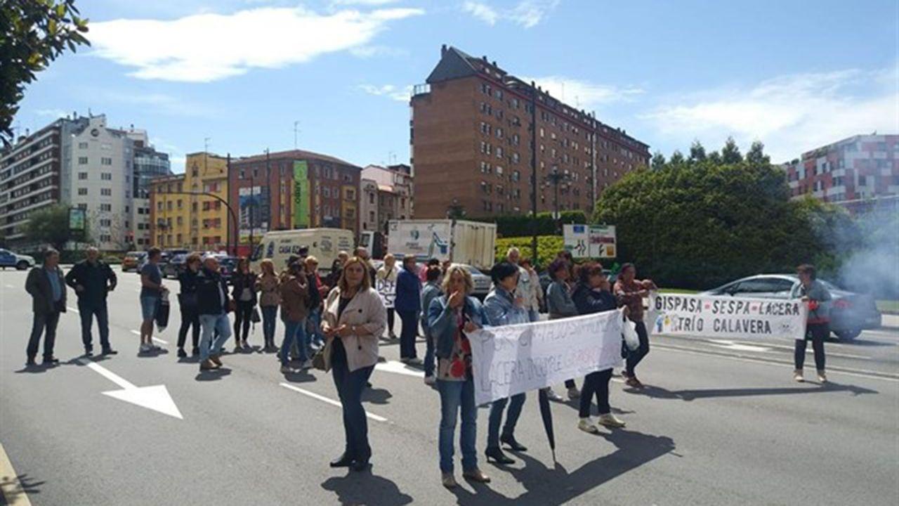 Un grupo de pacientes consulta la ubicación de los servicios en las consultas externas del HUCA.Los trabajadores de limpieza del HUCA cortan la carretera en Oviedo