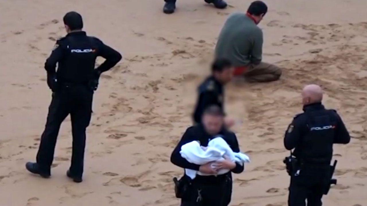 Un agente mantiene al bebé en brazos mientras otros vigilan al padre, arrodillado en la arena de San Lorenzo