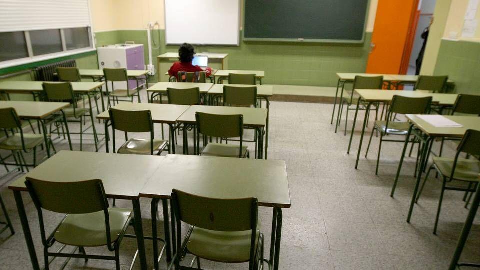un alumno en un aula, clase, vacía.Un hombre ataviado con una máscara sanitaria pasa frente a una oficina pública de empleo cerrada, en Oviedo.