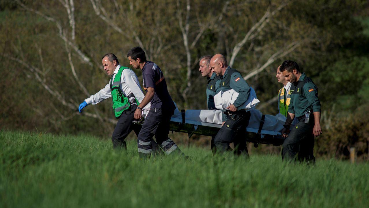Miembros del Servicio Judicial y de la Guardia Civil trasladan el cuerpo sin vida del hombre fallecido en Bande