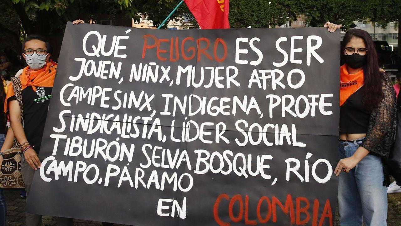 Jóvenes sostienen una pancarta de protesta durante una manifestación contra las masacres este viernes en Bogotá (Colombia)