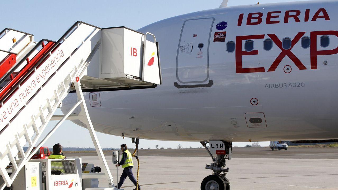 Un grupo de pasajeros consulta los vuelos en el Aeropuerto de Asturias.Un avión de Iberia Express