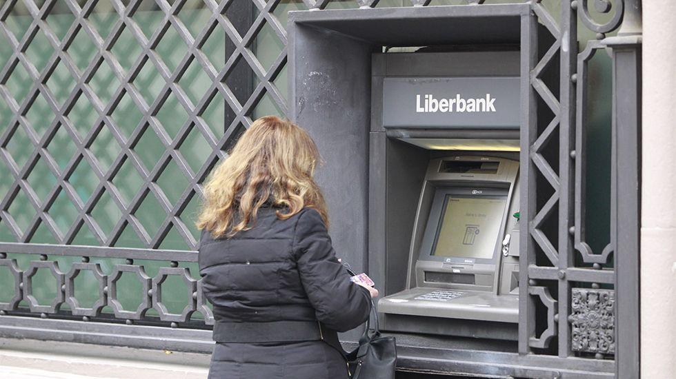 Escape en las baterias de coque de Avilés de Arcelor.Una mujer saca dinero en un cajero de Liberbank