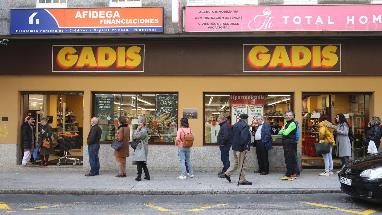 Colas manteniendo el metro recomendado de distancia de seguridad en un supermercado de Santiago