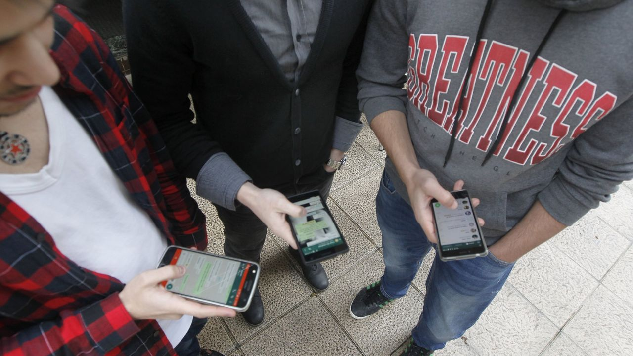JÓVENES USANDO LA APLICACIÓN DE WHATSAPP DE SU TELÉFONO MÓVIL