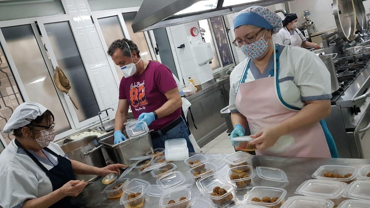 Cadena humana hostelera para repartir alimentos.Equipo de la Cocina Económica de Gijón prepara tuppers con raciones para la comida