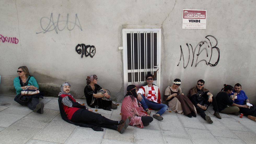 Visitantes de la feria se toman un descanso a la sombra junto a los puestos de comida de A Régoa