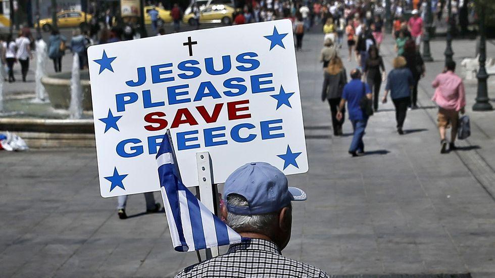 El extraño comportamiento de Juncker en la cumbre de Riga.Un hombre pasea por la plaza de Syntagma de Atenas con un cartel que apela a la ayuda divina para Salvar a Grecia.