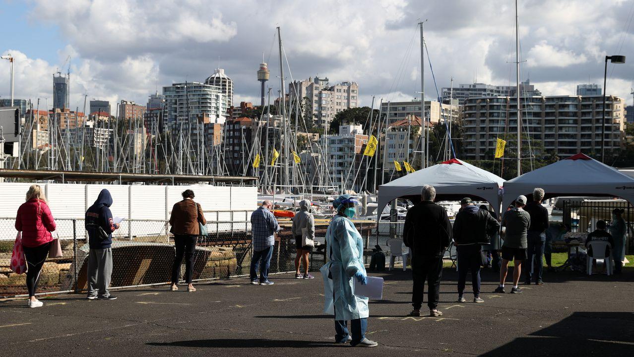 Las personas mantienen la distancia social mientras hacen cola para hacerse la prueba de la enfermedad del coronavirus en un centro de pruebas emergente, mientras el estado de Nueva Gales del Sur se enfrenta a un brote de nuevos casos, en Sydney, Australia