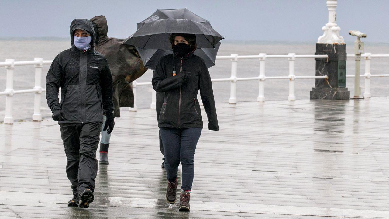 magno.Un grupo de personas pasea por la playa de San Lorenzo de Gijon, bajo la lluvia y el viento