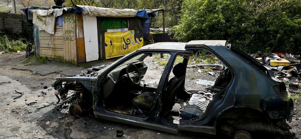 Detalle del esqueleto de un vehículo junto a una de las chabolas.