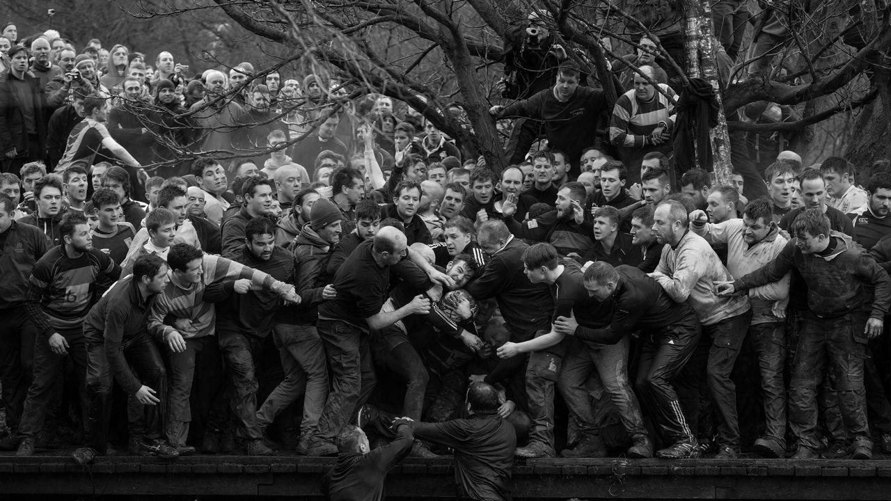 Fotografía cedida por la organización World Press Photo que muestra la imagen captada por el fotógrafo Oliver Scarff, ganador del primer premio de la categoría «Sports - Singles». La foto muestra a los miembros de equipos contrarios, los Up'ards y Down'ards, luchando por el balón durante el histórico y anual partido de fútbol Royal Shrovetide en Ashbourne, Derbyshire (Reino Unido), el 28 de febrero del 2017.