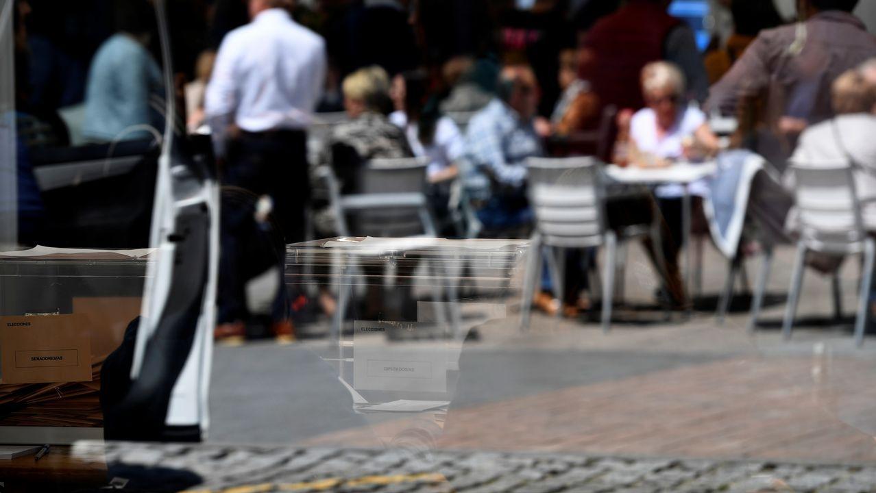 Reflejo de una urna de las votaciones a las elecciones generales, frente a una terraza, en Pola de Siero