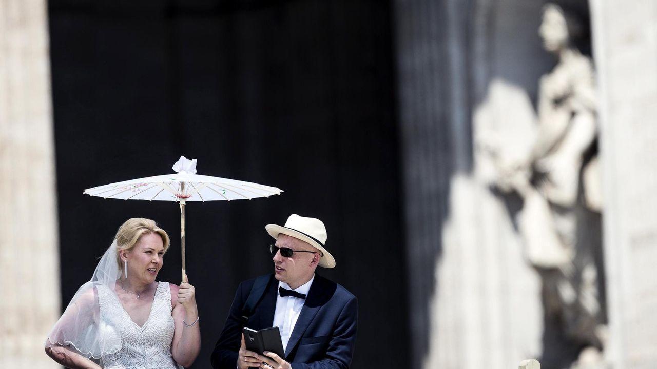 Una pareja de recién casados desafía el calor para asistir a la audiencia general semanal del papa Francisco en la plaza de San Pedro del Vaticano este miércoles
